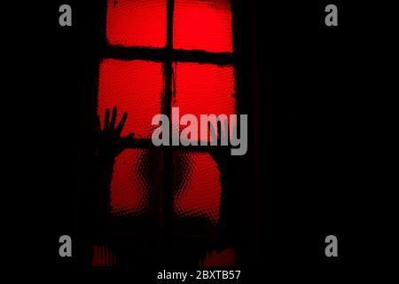 Unheimlich siduzing Person lehnt sich gegen Fenster in der Dunkelheit