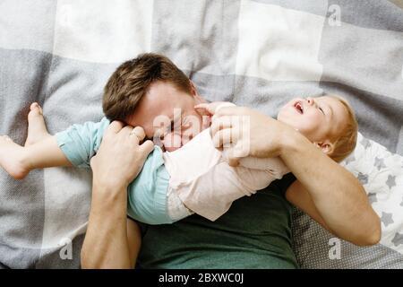 Draufsicht von liebevollen jungen Vater hält seine Baby-Tochter Kind und kitzeln sie, Vater`s Tag Konzept, liebevolle Familie - Stockfoto