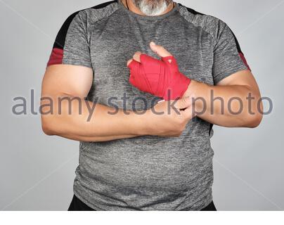 Athlet trägt graue Kleidung und wickelt seine Hände in Rot Textil elastische Bandage vor dem Training, grauer Hintergrund - Stockfoto
