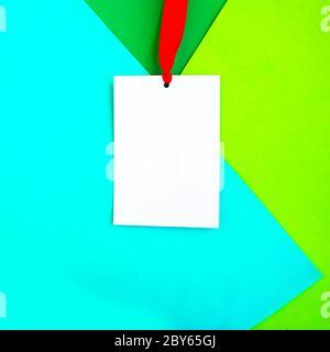 Weißes Mockup-Abzeichen mit rotem Band auf geometrischem grünem Hintergrund. Platz für den Text kopieren. Minimalkonzept - Stockfoto