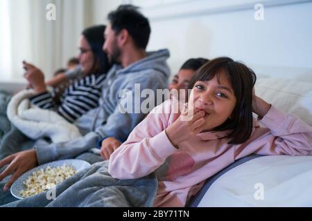 Portrait glücklich Mädchen essen Popcorn auf dem Sofa - Stockfoto
