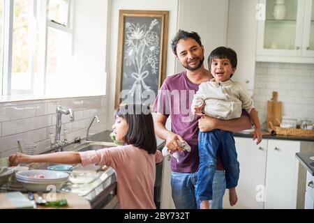 Portrait glücklicher Vater und Kinder beim Geschirr in der Küche - Stockfoto
