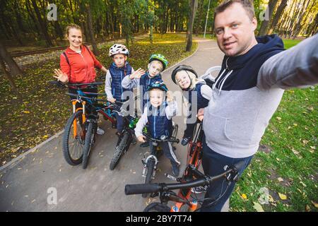 Das Thema Familie Sport Erholung im Freien. Große familie Kaukasischen 6 Personen Mama, Papa und 4 Kinder drei Brüder und Schwester fahren Fahrräder im Park auf - Stockfoto