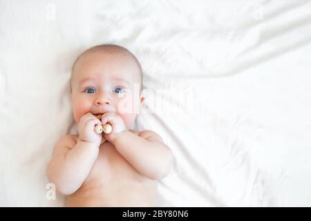 Nettes glückliches Baby, das mit hölzernen Öko-Perlen auf Weiß spielt Hintergrund