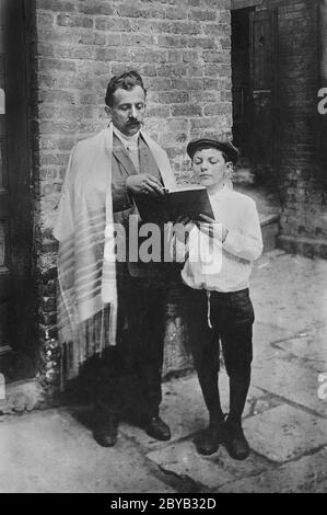 Rabbi und Junge lesen Buch, während sie draußen stehen, in der Nähe des Eingangs zum Gebäude am jüdischen Neujahr, New York City, New York, USA, Bain Nachrichtendienst, September 1907 - Stockfoto