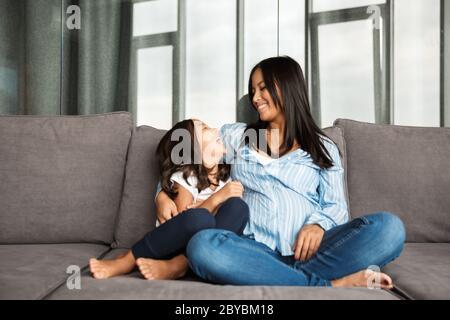 Foto von glücklich schwanger asiatische Frau mit ihrer kleinen Tochter umarmen und lachen, während sie zu Hause auf der Couch sitzen - Stockfoto