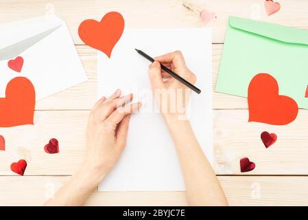 Girl's Hand schreibt einen Liebesbrief. Valentinstag. Handgefertigte Grußkarte mit einem roten Herz in Form einer Figur. Der 14. Februar ist ein Fest der - Stockfoto