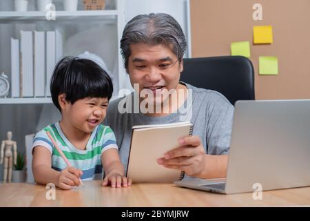 Asiatischer Vater, der mit einem Laptop im Home Office arbeitet und Hausaufgaben mit einer Tochter unterrichte. Neuer Lebensstil normal während einer Quarantäne. Konzept des Aufenthalts - Stockfoto