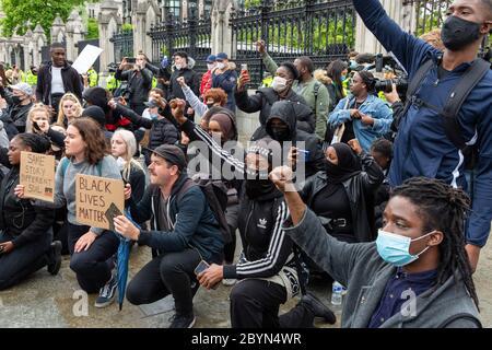 Demonstranten greifen während eines Black Lives Matters-Protests auf dem Parliament Square, London, 7. Juni 2020, ins Knie