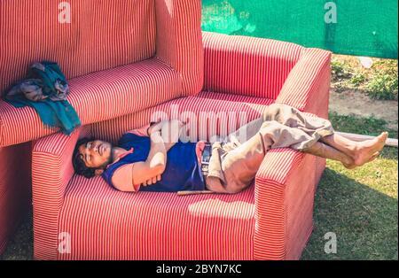Udaipur, Indien - 10 Feb. 2014 - Indischer Mann schläft und ruht auf Sessel im Freien - Stockfoto