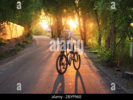 Frau, die im Sommer bei Sonnenuntergang auf der Landstraße Fahrrad fährt - Stockfoto