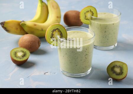 Zwei gesunde Detox Smoothie Kiwi und Banane in Gläsern auf hellblauem Hintergrund mit frischen Zutaten, Diät und Gewichtsverlust-Konzept, Closeup - Stockfoto