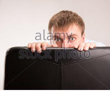 Ein junger Mann versteckt sich hinter einem Bürostuhl - Stockfoto