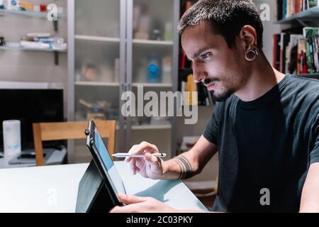 Profil eines Mannes mit Piercings, Bart und Schnurrbart mit einem Tablet mit einem digitalen Stift in einem Raum voller Bücher - Stockfoto