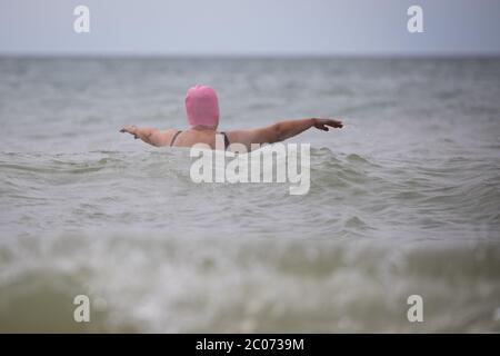 11. Juni 2020, Schleswig-Holstein, Westerland/Sylt: Eine Frau mit rosa Badekappe schwimmt in der Nordsee am Strand von Westerland auf Sylt. Foto: Christian Charisius/dpa