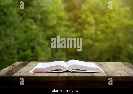 Öffnen Sie das Buch auf dem Holztisch im Garten - Stockfoto