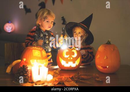 Liebenswert Kinder, Kleinkind Junge und Mädchen, spielen mit Halloween geschnitzten Kürbis und Dekoration zu Hause - Stockfoto