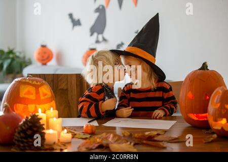 Liebenswert Kinder, Kleinkind Junge und Mädchen, spielen mit Halloween geschnitzten Kürbis, küssen freundlich - Stockfoto