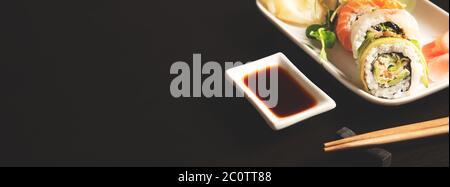 Sushi-Rolle auf Teller. Japanische asiatische traditionelle Küche, Vorderansicht. Webbanner Hintergrund mit Kopierplatz - Stockfoto
