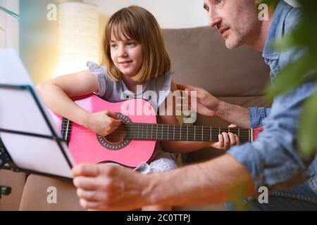 Kleines Mädchen lernen, Gitarre zu Hause mit einem Lehrer in Privatstunden sitzen auf dem Wohnzimmer Sofa aus der Nähe zu spielen Stockfoto