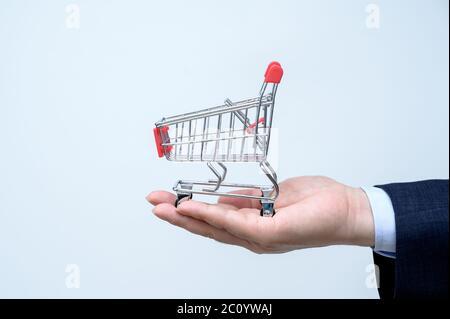 Mann im Anzug mit kleinem Einkaufswagen in der Hand. Nahaufnahme. Business, Commerce und Shopping Konzept. - Stockfoto
