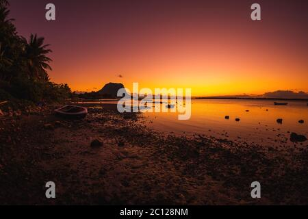 Fischerboot, ruhiges Meer und farbenfroher Sonnenuntergang. Le Morn brabant Berg in Mauritius.