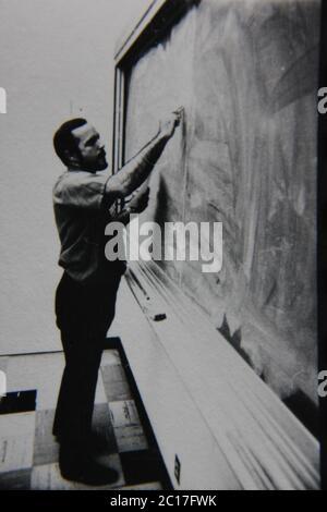 Feine 70s Vintage schwarz-weiß extreme Fotografie eines Lehrers, der an der Tafel steht und darauf schreibt.