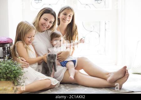 Junge hübsche Frau und Töchter spielen mit Kätzchen - Stockfoto