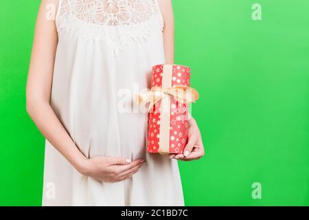 Nahaufnahme Porträt der schwangeren Frau in weißem Kleid mit einer Geschenkbox auf grünem Hintergrund. Schwangerschaftsfeier. Speicherplatz kopieren. - Stockfoto
