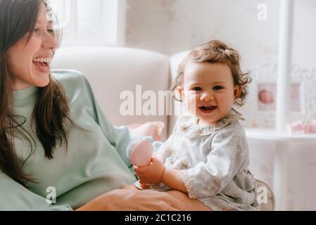 Kleines Mädchen mit Spaß sitzen auf ihre schwangere Mutter im Zimmer Stockfoto