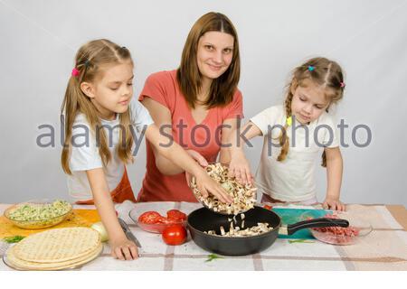 Zwei kleine Mädchen auf dem Küchentisch mit einem Eifer zu helfen, ihre Mutter die Pilze aus der Platte in die Pfanne gießen - Stockfoto