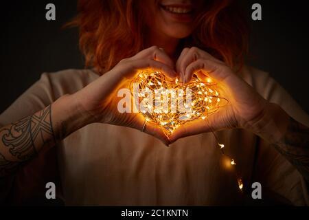 Happy rothaarige Mädchen holding Girlande in der Form von Herzen auf einem dunklen Hintergrund. Festliche Karte