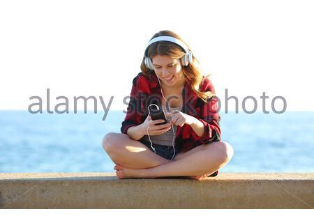 Volle bofy Vorderansicht Portrait von ein Jugendmädchen Durchsuchen von Musiktiteln auf smart phone Musik am Strand - Stockfoto