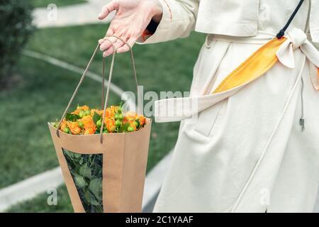 Nahaufnahme junge Erwachsene Mode edle Frau model Hand mit authentischen frischen orangen Sprayrosen Blumenstrauß verpackt in Handarbeit Papiertasche auf der Stadt - Stockfoto