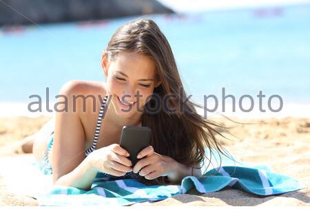 Glückliches Mädchen im Bikini mit smart phone liegen auf einem Handtuch am Strand im Sommerurlaub - Stockfoto