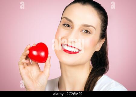 Schöne lächelnde Frau hält ein wenig rotes Herz in der Hand auf rosa Hintergrund, Liebe Konzept. - Stockfoto