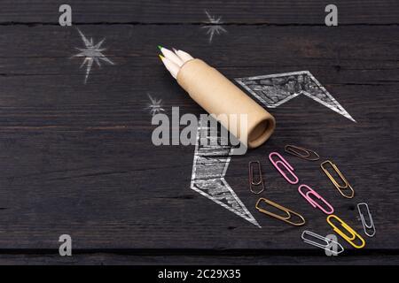 Schule Schreibwaren Bürobedarf und Hand gezeichnet Rakete auf dunklem Hintergrund. Zurück zum Konzept der Schule. Neue Idee und Kreativität starten Stockfoto