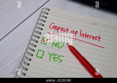 Interessenkonflikt auf eine Haftnotiz schreiben. Unterstützt durch einen zusätzlichen Service isoliert Holztisch. - Stockfoto