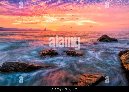 Ein Sonnenuntergang am Meer mit einem lebendigen bunten Himmel und EIN Segelboot Segeln wie Vögel fliegen in der Ferne