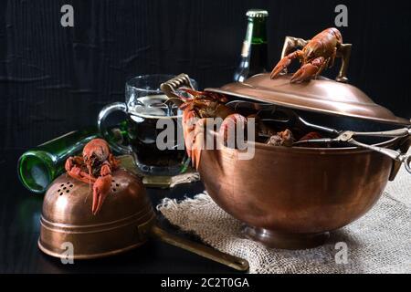 Luxury Seafood Dinner: In einem alten Kupfertopf werden Krebse und ein Glas Craft-dunkles Bier zubereitet - Stockfoto
