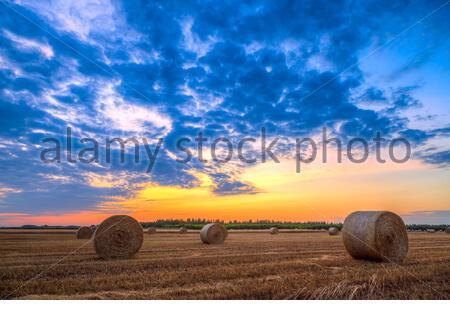 Sonnenuntergang über Feld-Hof mit Heuballen