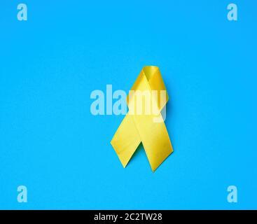 Gelbe Band auf einem blauen Hintergrund, Symbol des Kampfes gegen die Katze Tumor, Problem der Selbstmorde und ihre Prävention, in der Nähe - Stockfoto
