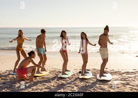 Multiethnische Gruppe von Männern und Frauen, Surfen am Strand