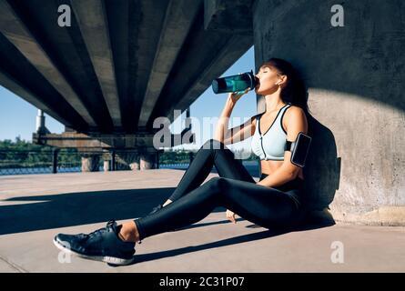 Junge Fitness Frau Trinkwasser aus der Flasche