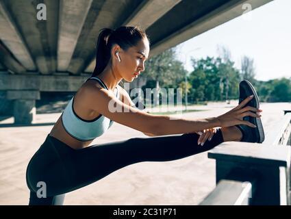 Sportliche Läuferin, die die Beine dehnt, um sich vor dem Training aufzuwärmen Stockfoto
