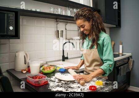 Junge afroamerikanische Frau macht in ihrer Küche Kekse. - Stockfoto