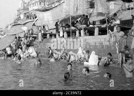 Hindus am Ganges in Benares, auch bekannt als Varanasi oder Kashi, im Bundesstaat Uttar Pradesh. Der Legende nach ist die mehr als 2500 Jahre alte Stadt die Stadt Shiva, eine der wichtigsten Hindu-Gottheiten. Die Hindus glauben, dass die Menschen, die hier sterben, den ewigen Kreislauf der Wiedergeburten durchbrechen und Erlösung erlangen können, so viele Gläubige kommen nach Benares, um hier zu sterben. - Stockfoto