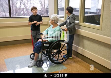 Enkel besuchen Großmutter im Krankenhaus - acht und neun Jahre alte mexikanisch-amerikanische Jungen besuchen ihre im Rollstuhl gebundene ältere Großmutter im Krankenhaus in Austin, Texas. © MKC / Daemmrich Fotos - Stockfoto