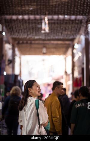 Dubai / Vereinigte Arabische Emirate - 1. Februar 2020: Schöner junger asiatischer Tourist, der durch den überdachten Basar-Einkaufsmarkt in Downtown Burj Dubai spazierengeht