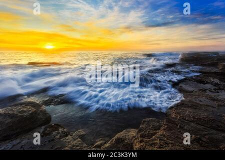Einfallende Welle auf Sandsteinfelsen des Turimetta Strandes um die Narrabeen Landzunge bei Sonnenaufgang an der pazifikküste in Sydney. - Stockfoto